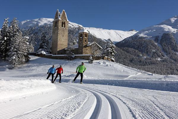 Engadin St. Moritz - Langlaeufer vor der Kirche San Gian